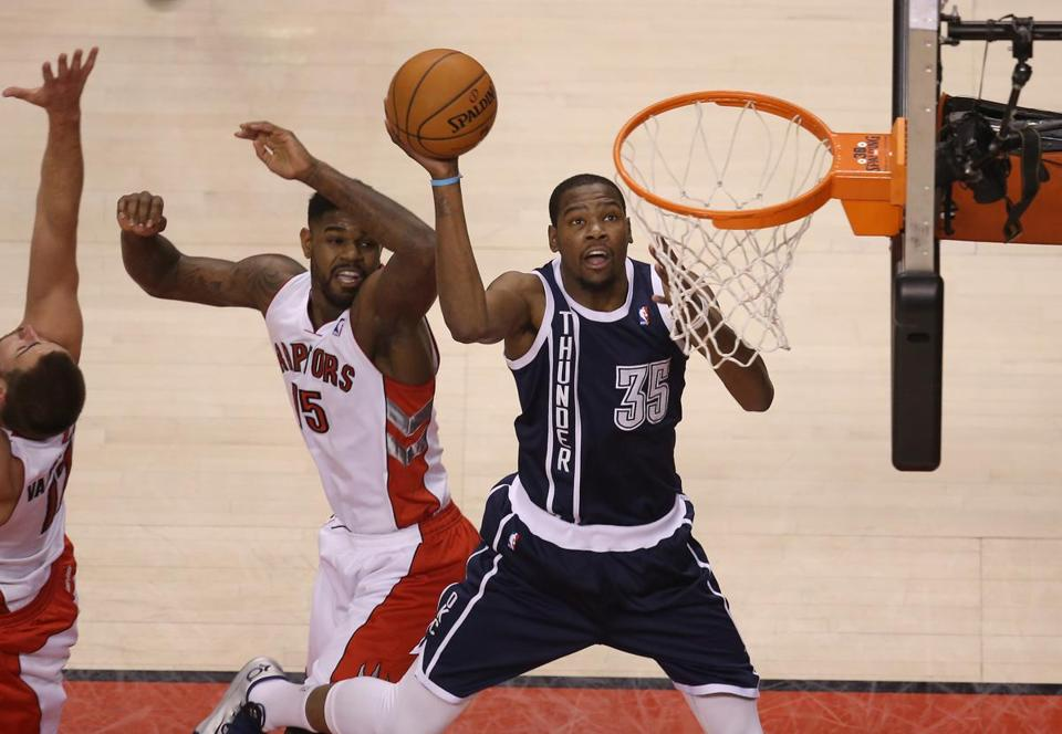 Oklahoma City Thunder forward Kevin Durant (35) went to the basket and scores past Toronto Raptors forward Amir Johnson (15) at Air Canada Centre.